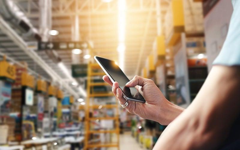 Operador de fábrica com telemóvel a identificar diversos bens no armazém